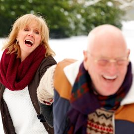 Older couple running in snow