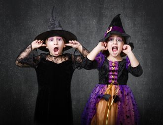 girls dressed for Halloween covering ears